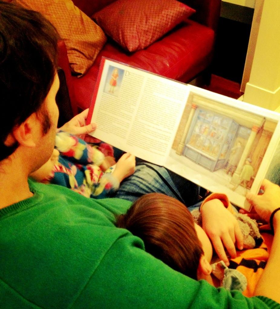 """Lieblingspapa liest den zwei Kleinen vor. Goldmädchens Lieblingsweihnachtsbuch: """"Holly und Ivy""""."""