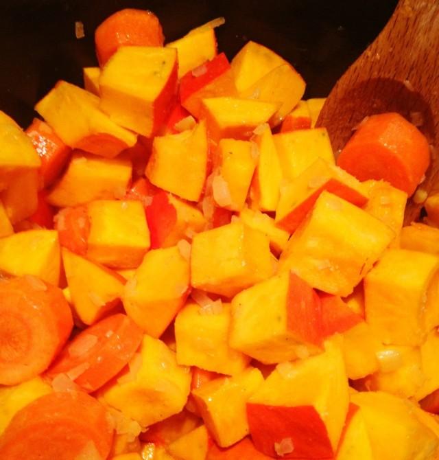 Kürbiswürfel, Karottenstücke, Ingwer und Zwiebeln beim Andünsten