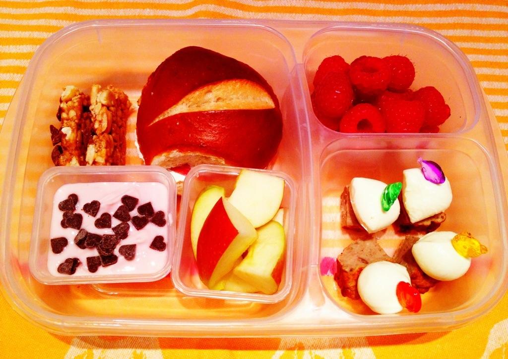 Easylunchbox im Test an Tag 2: belegte Laugenkastanie, Erdbeerjoghurt mit Schokoherzchen, Apfelschnitze, Müsliriegel, Minikebap mit Mozzarella und Bulette,  Himbeeren.