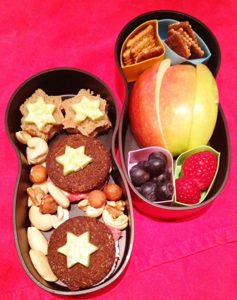 Blitzbefüllte Matroschkabox fürs Herzensmädchen: belegte Pumpernickeltaler mit Gurkensternchen, gemischte Nüsse, Obst in Silikonförmchen, Apfelschnitze, Mini-Leibnitz-Kekse.