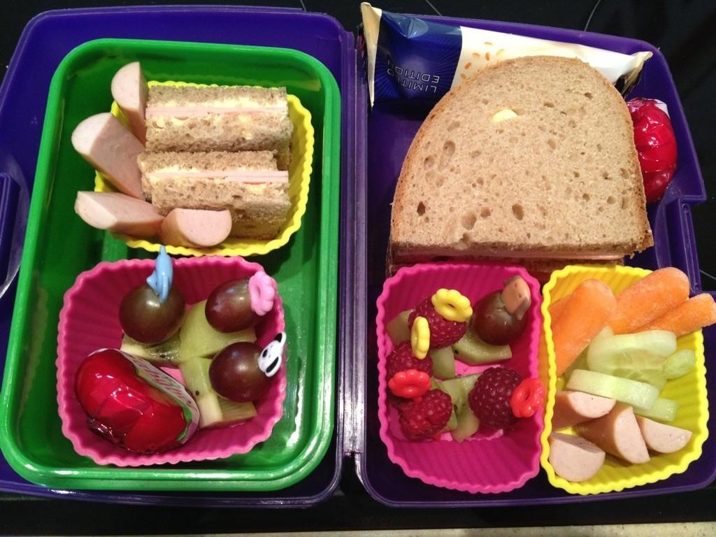 Zwei simple Bentos. Links Goldkinds Raupe-Nimmersatt-Box mit Babybel, Fruchtspießen, Brot und Geflügelwiener. Rechts Herzensmädchens Tchibo-Box mit Fruchtspießen, Brot, Minimöhren, Müsliriegel, Babybel, Gurkenfischchen und Geflügelwiener.
