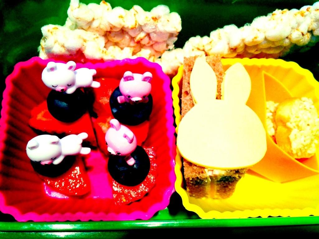 Kleines Goldkind-Bento in ihrer Raupe-Nimmersatt-Box mit Fruchtspießchen, Brot, Gouda in Miffyform, Minizwieback und Reiswaffel.