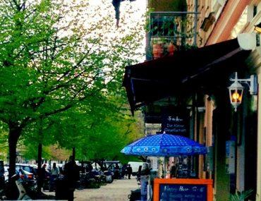 Rykestraße, Straßenansicht mit Bäumen, blauer Sonnenschirm vor der Kleinen Gesellschaft