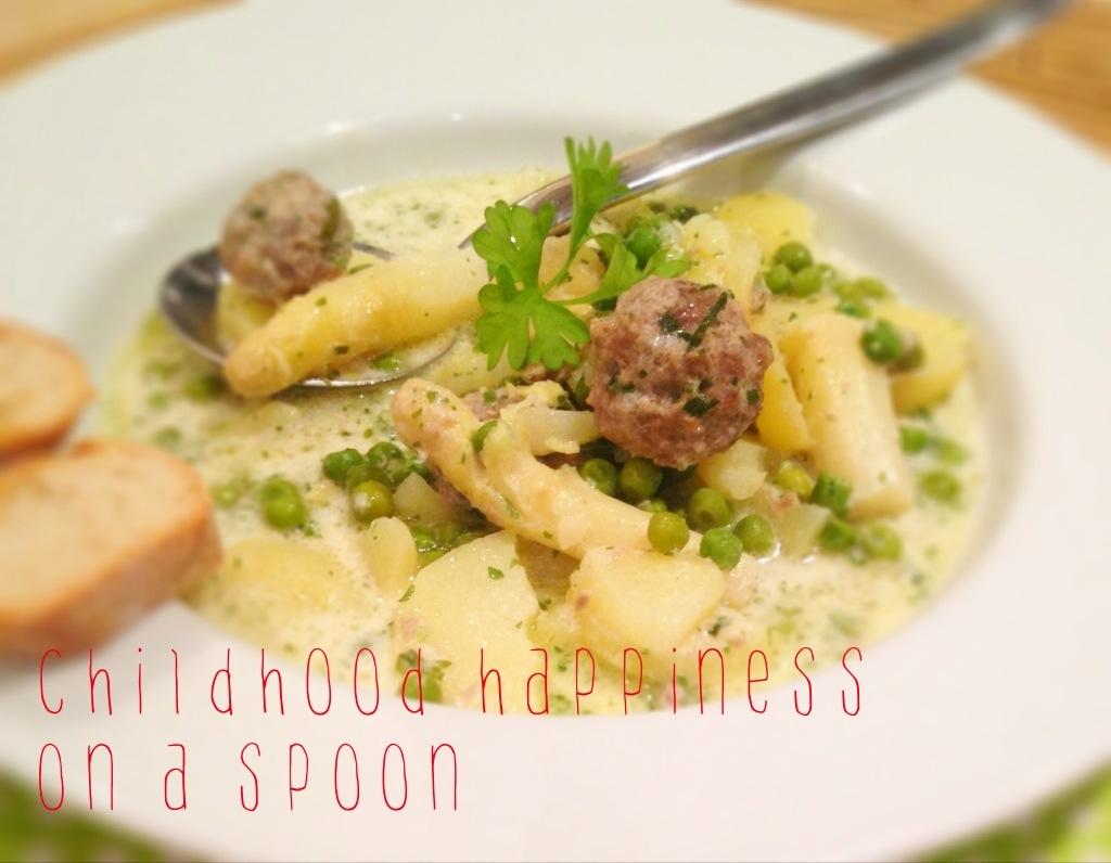 """fertige Suppe auf dem Teller, angerichtet mit Kräutern und der Aufschrift """"childhood happiness on a spoon"""""""