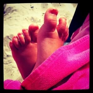 Kleinkindfüße in Nahaufnahme , im Hintergrund Strand, im Vordergrund ein pinkes Handtuch