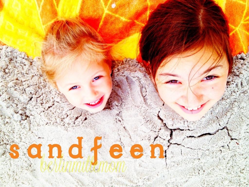 Zwei Mädchen, eins kleines blondes, ein größeres dunkelhaariges, bis zum Hals eingegraben, die lachend nach oben in die Kamera schauen.