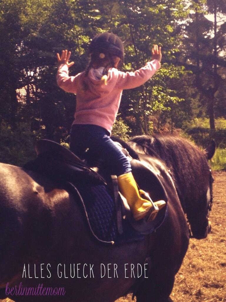Nahaufnahme von einem kleinen Mädchen in rosa Jacke und mit Reithelm im sogenannten leichten Sitz auf einem schwarzen Pferd, Ansicht seitlich-von hinten.