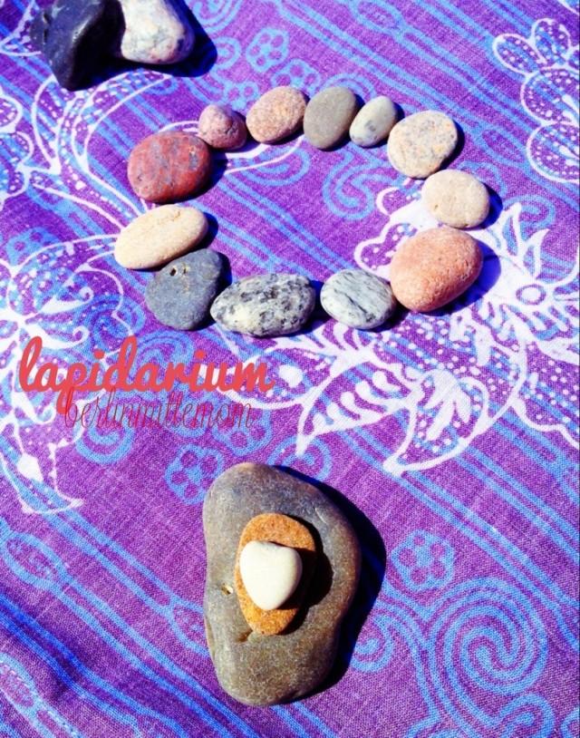 Nahaufnahme von auf einem bunten Tuch arrangierten Ostseesteinen, im Vordergrund gestapelte Steine, im Hintergrund ein kleiner Kreis aus Steinen