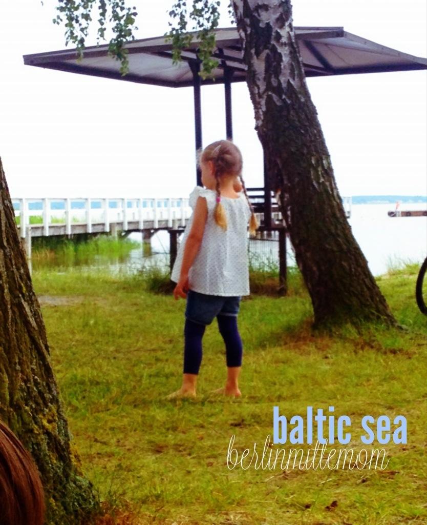 Kleines Mädchen von hinten fotografiert, am Bodden in Wieck aufgenommen, im Hintergrund der Bodden mit Steg