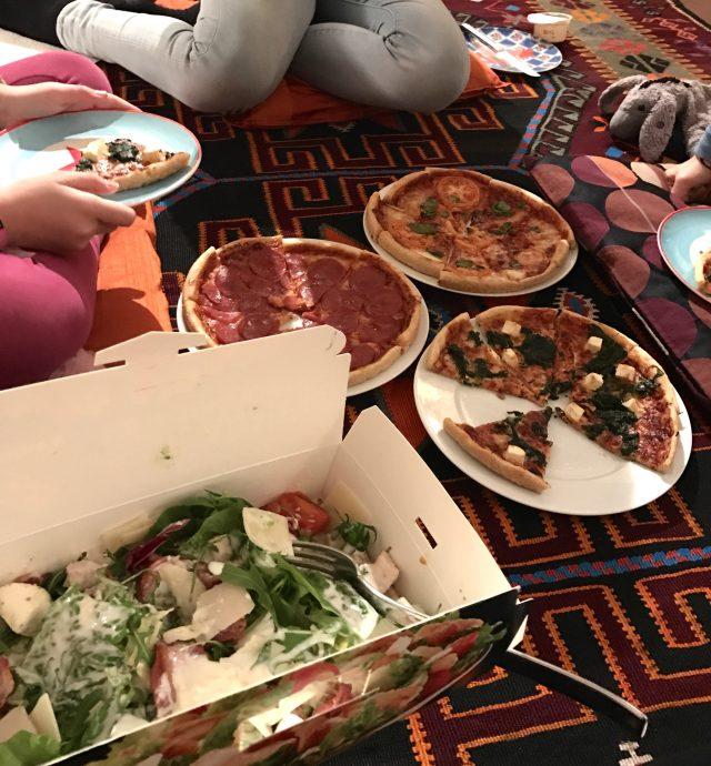 Fußbodenpicknick mit Pizza und Kinderquatsch